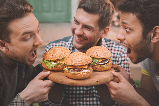 Side view of excited young men biting fresh tasty hamburgers stock photo