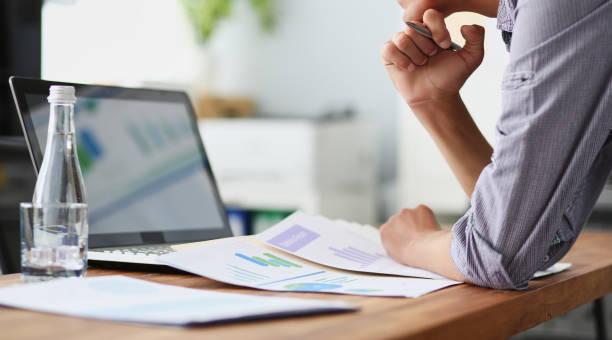 Seitenansicht eines erfahrenen Geschäftsmannes, der Finanzdaten mit Grafiken und Diagrammen betrachtet, während er an einem Laptop arbeitet. – Foto