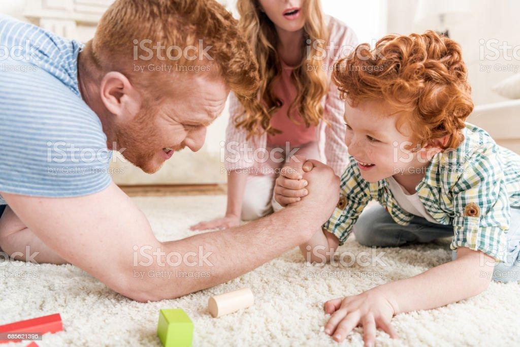 아버지와 아들이 팔 씨름 근처 어머니 집에서 가족 재미에 의해 개념을 연주의 측면 보기 royalty-free 스톡 사진