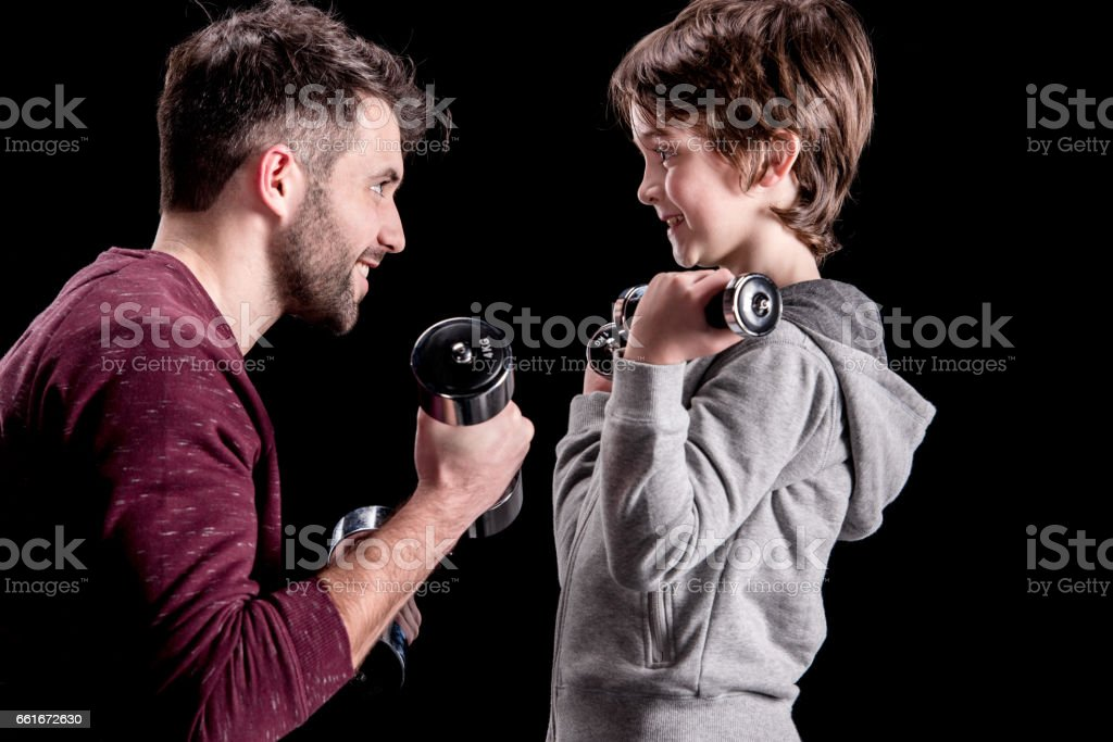 Side view of father and son training with dumbbells and looking at each other stock photo