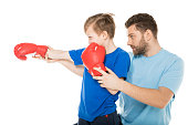 Side view of father with son boxing together isolated on white