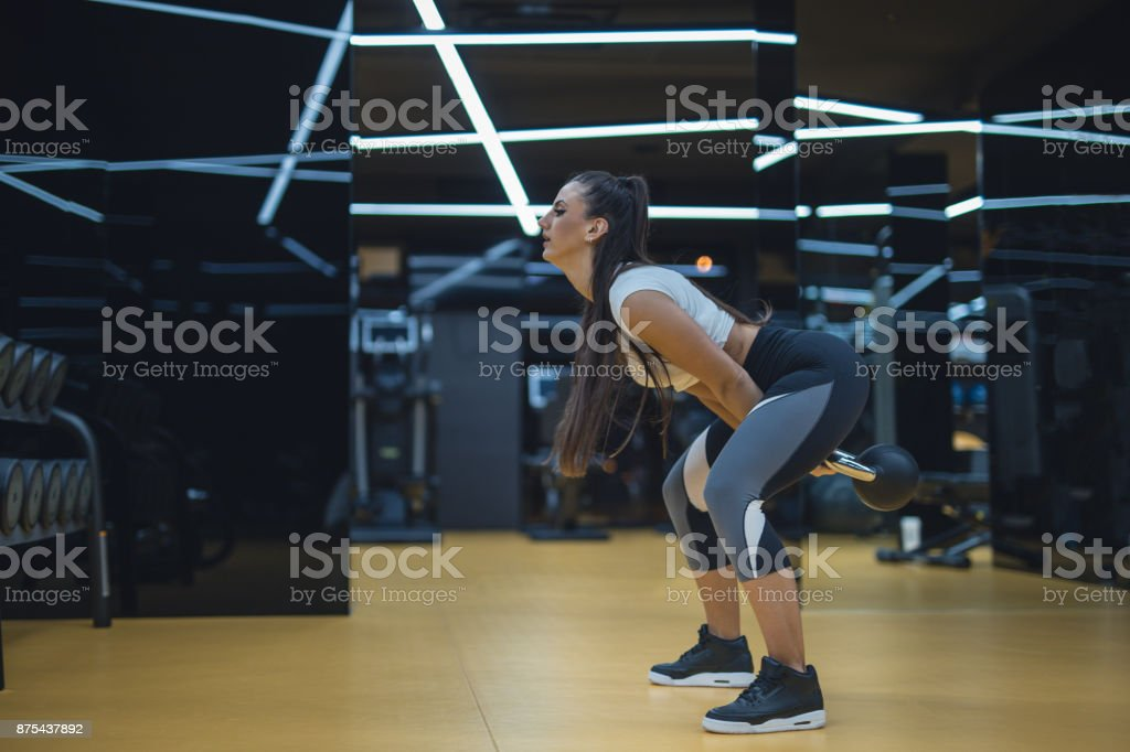 Side view of female doing weights at luxury gym stock photo