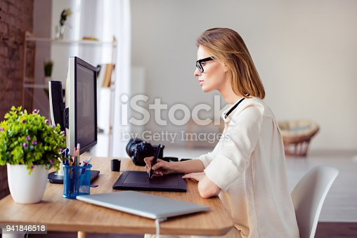 istock Side view  of female graphic designer working with interactive pen display, digital drawing tablet and pen on a computer in workstation 941846518