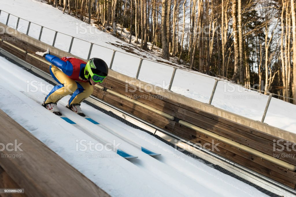 Side View of Female Ski Jumper at Inrun stock photo