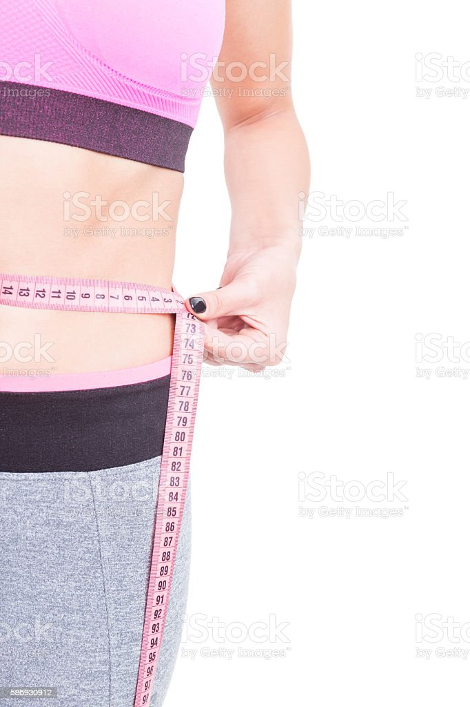 Side view of fit woman waist with tape line stock photo