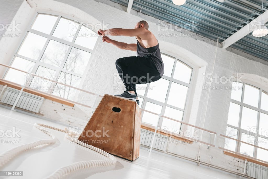 Side view of fitness male athlete jumping through at square box in...