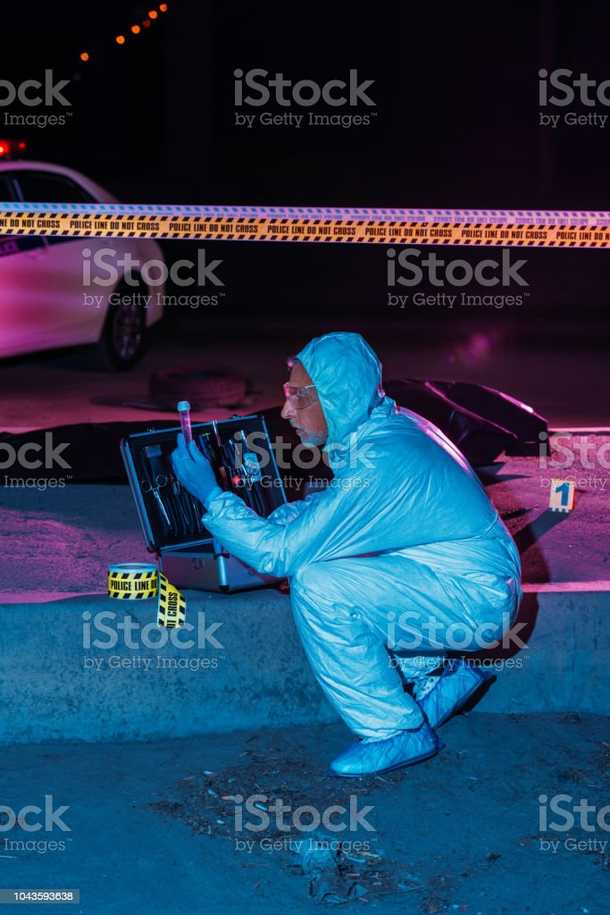 side view of focused male criminologist in protective suit and latex gloves collecting evidence at crime scene with corpse stock photo