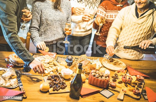 1064325668 istock photo Side view of friends group tasting christmas sweets food and having fun at home drinking champagne sparkling wine - Winter holidays concept with people enjoying time eating together - Warm filter 1064325668