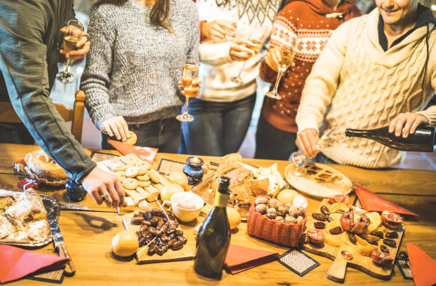 side view of friends group tasting christmas sweets food and having fun at home drinking champagne sparkling wine - winter holidays concept with people enjoying time eating together - warm filter - party social event stock pictures, royalty-free photos & images