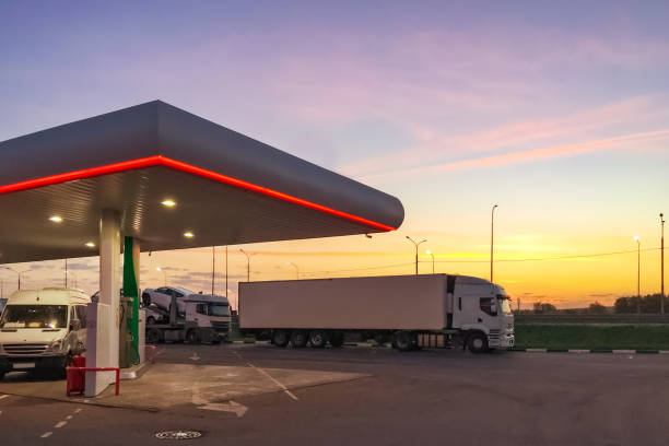 side view of gas station fueling with cars standing on it and white truck at sunset or early morning time. - stacja benzynowa zdjęcia i obrazy z banku zdjęć