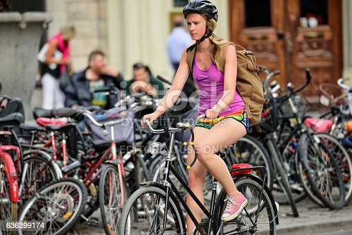 583973114istockphoto Side view of girl bicycle. Wearing colorful training clothes, helmet 636399174