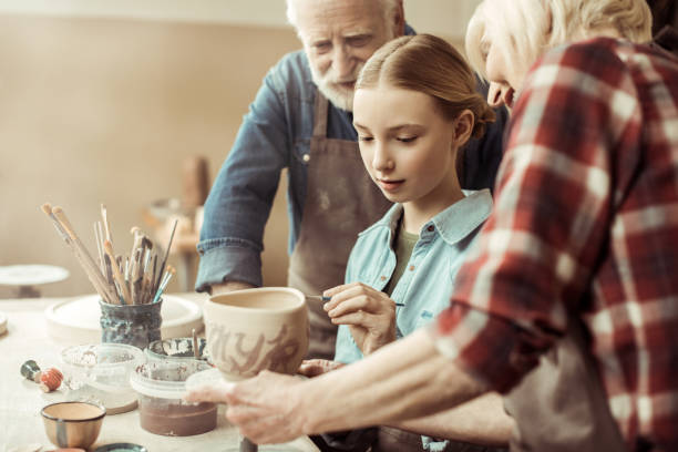 seitenansicht der mädchen malerei tontopf und großeltern helfen beim workshop - handbemalte teller stock-fotos und bilder