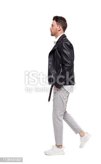 Side view of going  handsome man in a leather jacket and trousers. walking young guy . people collection.  backside view of person.  Isolated over white background. The rocker goes past the frame