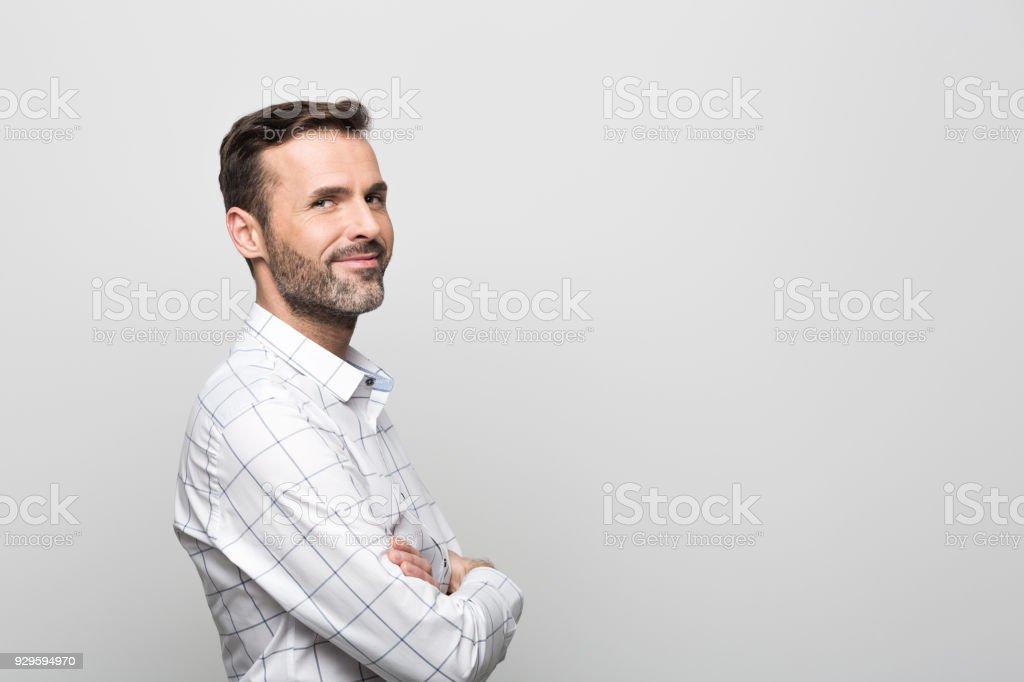 Seitenansicht des schönen Geschäftsmann lächelnd in die Kamera, grauen Hintergrund – Foto