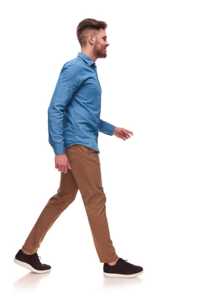 side view of handsome casual man walking - walking stock pictures, royalty-free photos & images