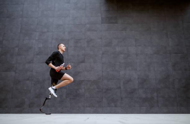 sida syn på snygg passform kaukasiska sportsman med konstgjorda ben som löper utanför. - protesutrustning bildbanksfoton och bilder