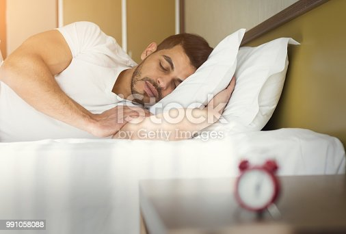 istock Side view of handsome man sleeping in bed 991058088