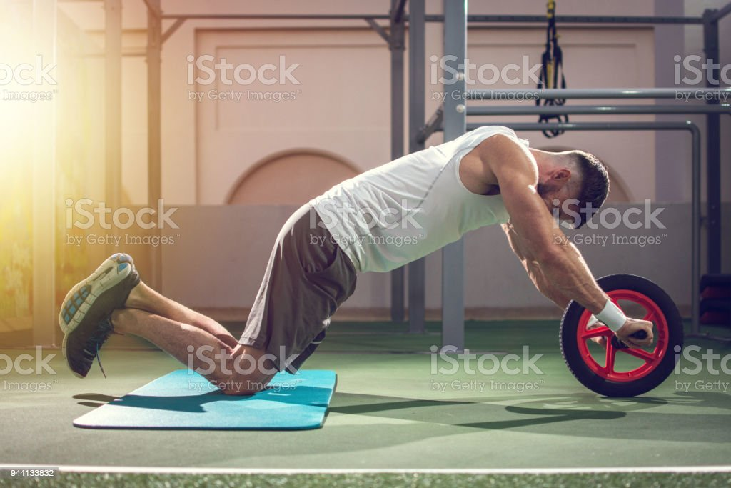 Side view of handsome man working out with fitness wheel in gym stock photo