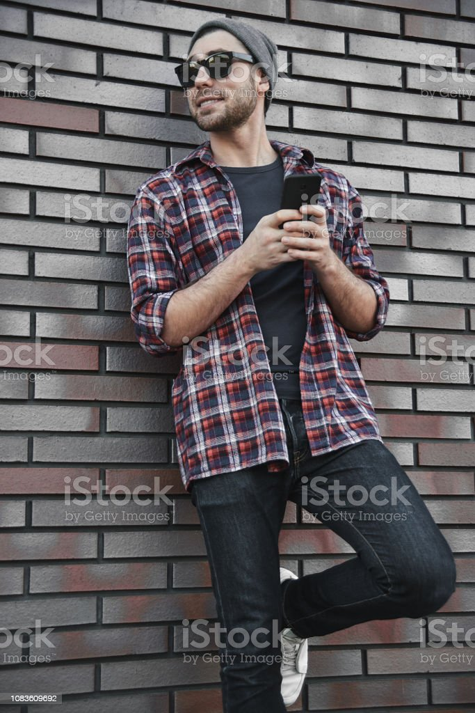 Hipster sms texting phone app in city street on brick wall...