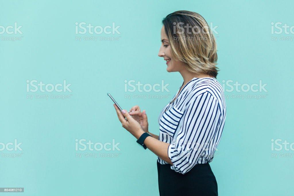 Seitenansicht des Glücks Business-Frau, allein am blauen Wand bestraft und mit Smartphone. – Foto