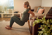 istock Side view of happy athlete doing triceps dips while leaning on the sofa at home. 1296101886