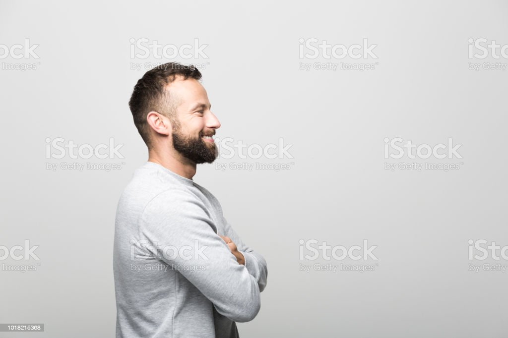 Side view of happy bearded young man standing with arms crossed Side view of smiling bearded young man standing with arms crossed against grey background. 30-34 Years Stock Photo