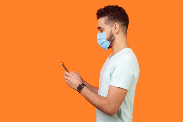 Side view of happy brunette man with surgical medical mask smiling while using cellphone, chatting in social media, enjoying mobile service. stock photo