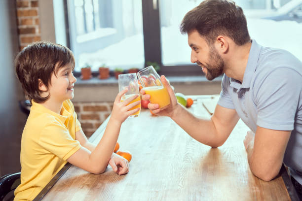 Side view of happy father and son drinking fresh juice together stock photo
