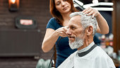 istock Side view of happy handsome bearded man getting haircut at barbershop. Young barber girl working with hair clipper 1226825647