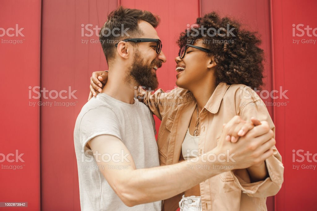 side view of happy young multiethnic couple dancing and holding hands royalty-free stock photo