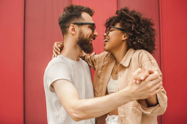 Seitenansicht des jungen multiethnischen Brautpaar tanzen und Hand in Hand – Foto