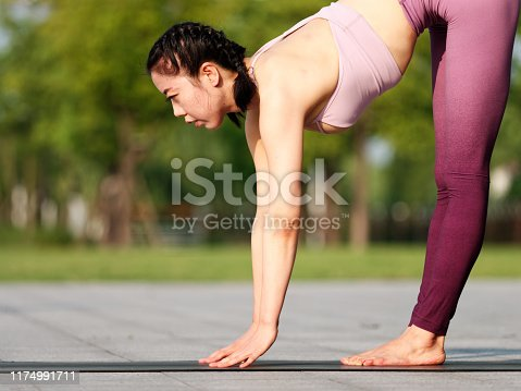 Side view of healthy women in sportswear practicing yoga outdoor. Standing forward bend exercise working out wearing sportswear pink top and pants, warming up exercises.