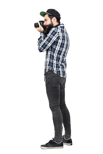 Side view of hipster taking photo with dslr camera Side view of hipster in plaid shirt and baseball cap taking photo with dslr camera. Full body length portrait isolated over white studio background. men in tight jeans stock pictures, royalty-free photos & images