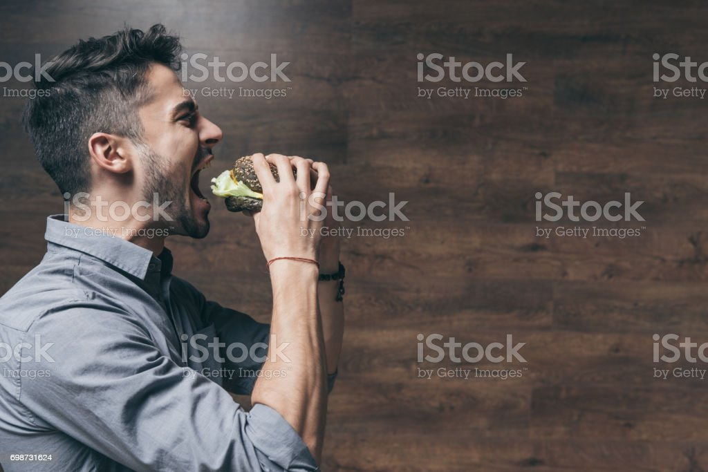Side view of hungry young man biting delicious hamburger stock photo