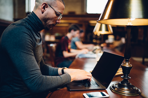 istock Side view of intelligent concentrated male scientist working online on modern laptop device using internet public connection, clever adult student in casual wear learning online in university library 1158476157