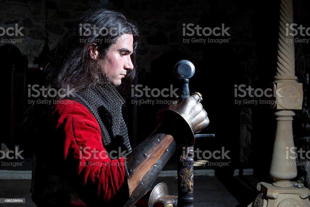 Side View of Knight With Sword Against Black Background stock photo