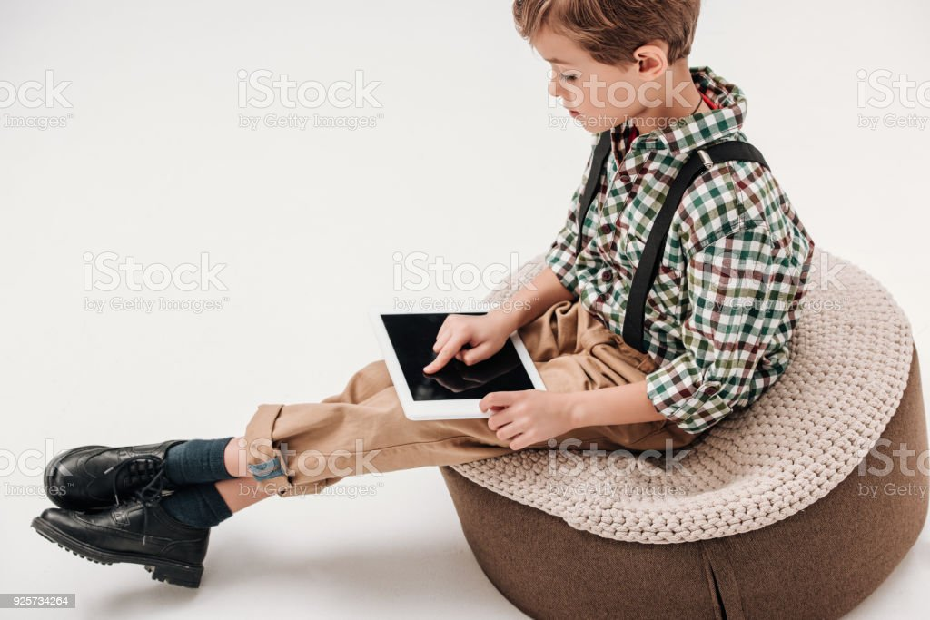 side view of little boy sitting and using digital tablet with blank screen isolated on grey stock photo