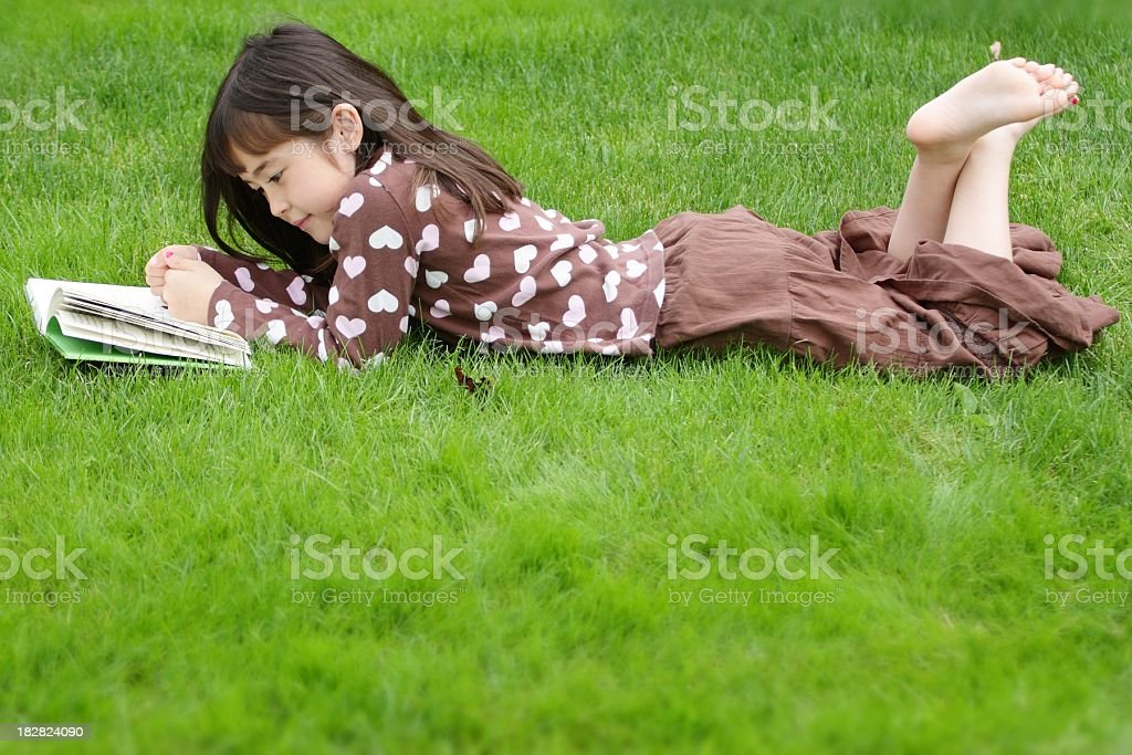 Side view of Little Girl Reading in Grass stock photo