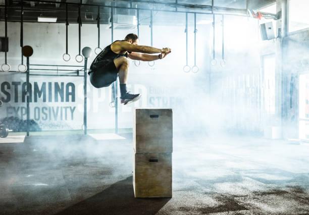 vista lateral do atleta masculino pulando na caixa durante o treinamento do esporte em uma academia. - esforço - fotografias e filmes do acervo