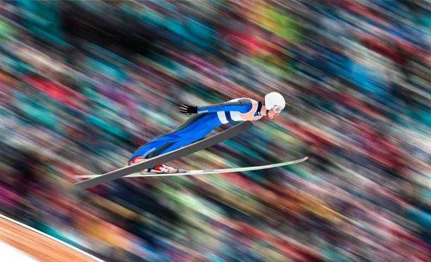 Seitenansicht des männlichen Skispringer in der Luft vor verschwommenen Hintergrund – Foto