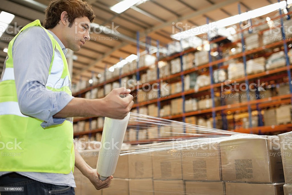 Side view of male warehouse worker wrapping cardboard cardboard boxes stock photo