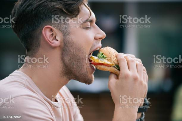 Side view of man eating tasty burger with closed eyes picture id1017325802?b=1&k=6&m=1017325802&s=612x612&h=115frrqz9c69kayehvahwsbsg utuln x2iaztcbgjq=