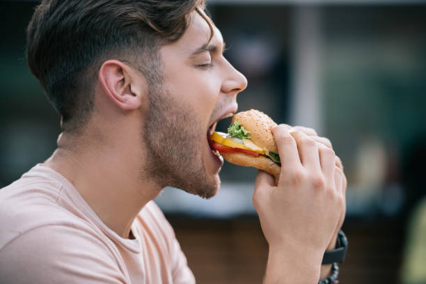 side view of man eating tasty burger with closed eyes - eating imagens e fotografias de stock