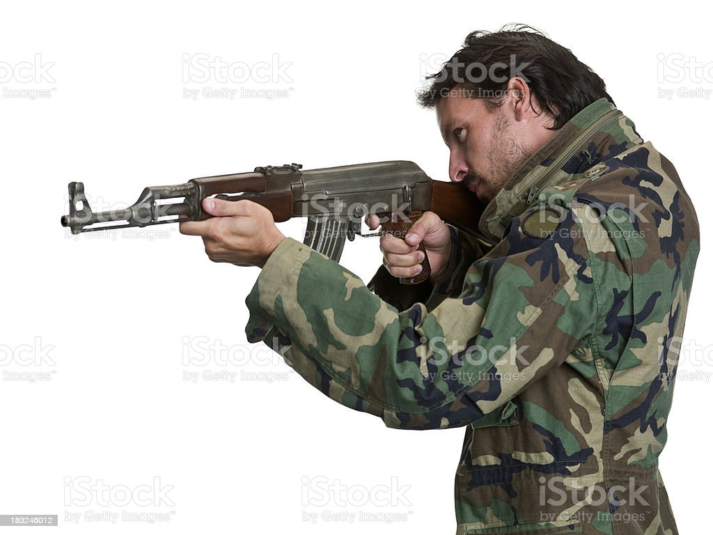 Side view of man holding a large gun wearing camouflage. royalty-free stock photo