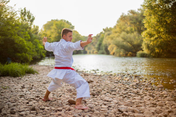 Side view of man praciticing karate in nature