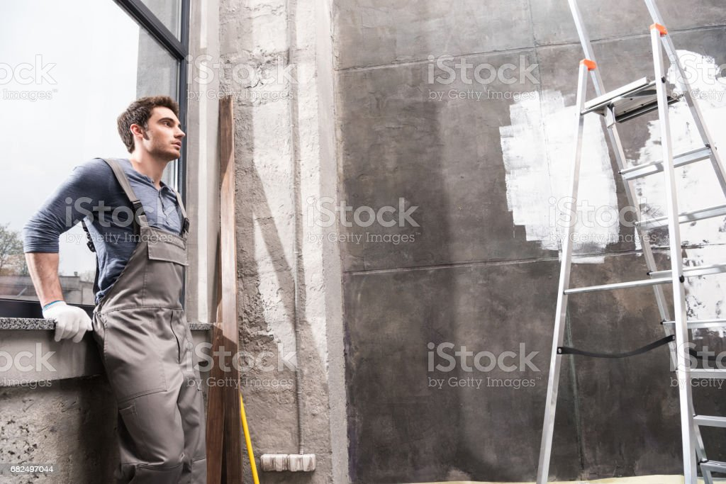 side view of man resting while renovating home, renovation home concept royalty-free stock photo