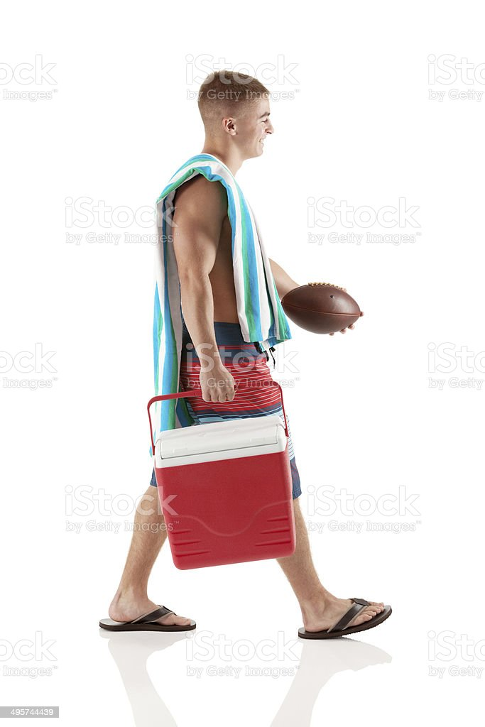 Side view of man walking with cooler and football stock photo