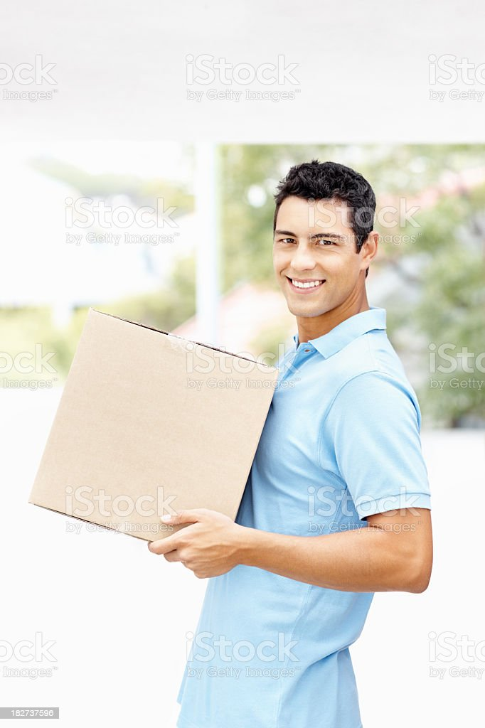 Side view of man with box moving into new house royalty-free stock photo
