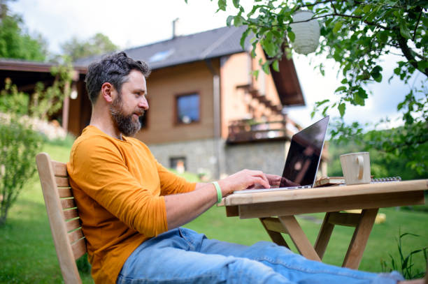 Side view of man with laptop working outdoors in garden, home office concept. stock photo
