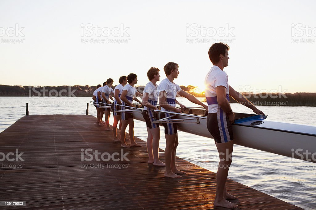 Side view of men holding boat royalty-free stock photo